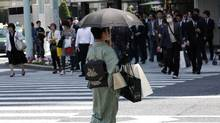 """A woman in a traditional """"Kimono"""" carries shopping bags at a shopping district. (KIM KYUNG-HOON/KIM KYUNG-HOON/REUTERS)"""
