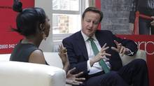 British Prime Minister David Camero, talks to young entrepreneurs Lenique Louis at the Prince's Trust headquarters in London as part of the government's launch of StartUp loans initiative and publication of Lord Young's report on enterprise, Monday, May 28, 2012. (Sang Tan/AP)