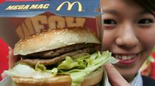 A McDonald's employee displays a Mega Mac burger at a McDonald's outlet in Tokyo April 5, 2007. (TOSHIYUKI AIZAWA/REUTERS)