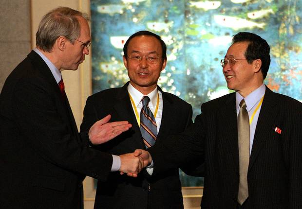 Christopher Hill, left, shakes hands with North Korean chief negotiator Kim Gye-gwan as South Korean deputy foreign minister Song Min-soon, middle, looks on at the close of talks over North Korea's nuclear crisis at the Diaoyutai state guest house in Beijing on Sept. 19, 2005.
