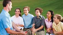 Young kids with a golf instructor
