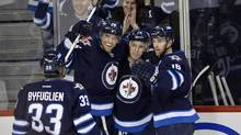 Winnipeg Jets' Bryan Little (C) celebrates his goal against the Tampa Bay Lightning with Dustin Byfuglien (33), Blake Wheeler (26) and Andrew Ladd (16) during the first period of their NHL hockey game in Winnipeg March 24, 2013. (FRED GREENSLADE/REUTERS)