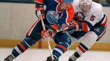 Edmonton Oilers' Wayne Gretzky and New York Islanders Denis Potvin (5) jostle for a loose puck during first period action at the Nassau Coliseum in New York on March 26, 1988. (CP)