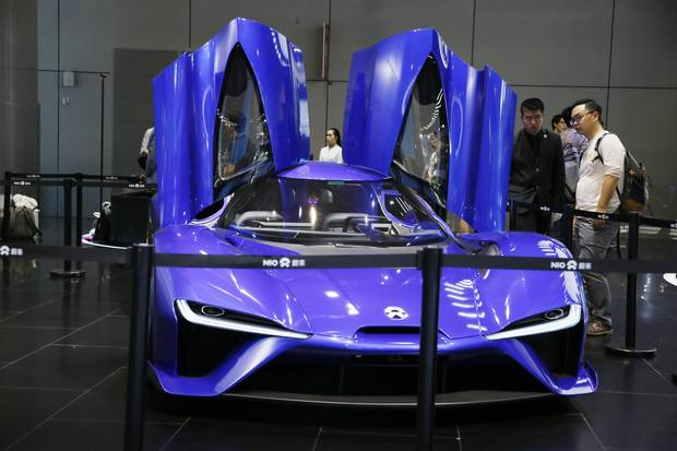 Visitors look at an electric sports car from Chinese startup NIO.