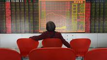An investor sits in front of an electrical board showing stock information at a brokerage house in Taiyuan, Shanxi province, on June 4, 2012. The Shanghai stock market slumped 2.7 per cent on Monday, its steepest drop in six months. (STRINGER/REUTERS)