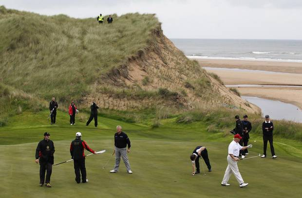 Donald Trump, in white shirt, plays golf during the opening of Trump International Golf Links near Aberdeen in 2012.