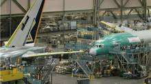 In this file photo, Boeing employees work on the 777 airplane assembly line. (Ted S. Warren/Ted S. Warren/AP)