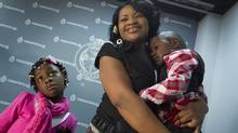 Biatra Muzabazi holds her children, Rene, 7, and Shane, 4, following a press conference at Police Headquarters in Toronto on Dec. 17, 2012. Toronto Police were influential in helping to the woman's children back after they were allegedly taken to Zimbabwe in April 2012 to spend their summer with their extended family, but were not allowed to return. (Peter Power/The Globe and Mail)