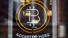 A Bitcoin sign is seen in a window in Toronto, May 8, 2014. (MARK BLINCH/REUTERS)