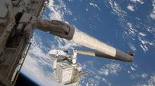 Backdropped by the Earth's oceans, the Space Shuttle Endeavour's Canadarm, controlled by Canadian astronaut Julie Payette, is about to hand off the Integrated Cargo Carrier (ICC) to the International Space Station (out of frame) on Sunday July 19, 2009. (HANDOUT/NASA/THE CANADIAN PRESS/HANDOUT/NASA/THE CANADIAN PRESS)