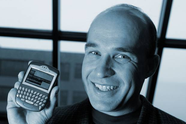 Nov. 5, 2003: Jim Balsillie, co-CEO of Research in Motion, holds a Blackberry 7230 showing The Globe and Mail's website. The BlackBerry was a pioneering Canadian achivement in mobile-phone technology, but it became known to its fans and detractors alike as the 'CrackBerry' for how addictive it could be to use.