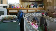 Ten-month-old Mylee stands in her crib in her home in Attawapiskat, Ont., Dec. 17, 2011. There are no plumbing or sanitary facilities in her residence. (Frank Gunn/THE CANADIAN PRESS)