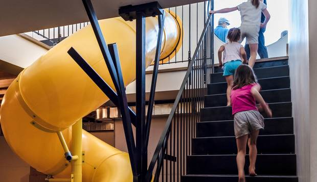 The slide, which cost $8,000, is positioned at a 'hinge point,' between the public rooms and the semi-private rooms.