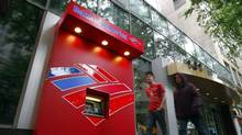 Pedestrians walk past a Bank of America ATM in Charlotte, North Carolina April 18, 2012. (CHRIS KEANE/REUTERS)