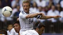 Vancouver Whitecaps Jay DeMerit heads the ball against the Houston Dynamo during the first half of their MLS game in Vancouver, British Columbia June 10, 2012. (BEN NELMS/REUTERS)