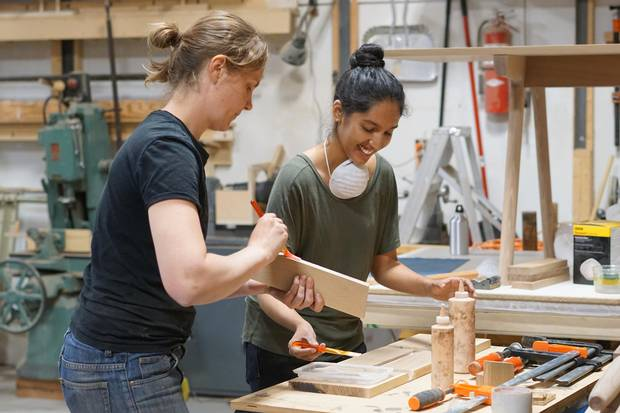 Carey Jernigan (left), co-founder of the Junction Workshop in Toronto, works with a student in the workshop.