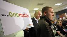 Huw Williams, left, and his life-saving stem cell donor Mike Hogman, right, talk to reporters upon the pair's first face to face meeting in the arrivals area of Pearson Airport in Toronto, Thursday April 28, 2011. The pair was brought together by the Onematch stem cell donor match network after Hogman read a post on Facebook. (J.P. MOCZULSKI/THE CANADIAN PRESS)