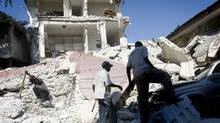 Men dig through the rubble of a collapsed building in downtown Port-au-Prince. (Peter Power/Peter Power/The Globe and Mail)