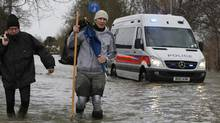 "Local residents carry belongings as they walk in the flooded part of the town of Staines-upon-Thames, England, while a police van patrols the area, Wednesday, Feb. 12, 2014. Prime Minister David Cameron insisted Tuesday that money is no object in the battle against the widespread flooding that has engulfed parts of England. Canceling a visit to the Middle East to oversee flood-fighting efforts, he told journalists that ""whatever money is needed for this relief effort will be spent"" as Britain deals with some of its wettest weather in 250 years. (Lefteris Pitarakis/AP)"