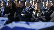 Israeli Prime Minister Benjamin Netanyahu, 3rd right and his wife Sara, 2nd right, Defence Minister Moshe Yaalon, 3rd left, and President Shimon Peres, front right, attend the joint funeral of the three Israeli teens who were abducted and killed in the occupied West Bank, in the Israeli city of Modiin Tuesday July 1, 2014. Tens of thousands of mourners converged Tuesday in central Israel for the funeral service for three teenagers found dead in the West Bank after a two week search and crackdown on the Hamas militant group, which Israeli leaders have accused of abducting and killing the young men. The deaths of Eyal Yifrah, 19, Gilad Shaar, 16, and Naftali Fraenkel, a 16-year-old with dual Israeli-American citizenship, have prompted angry calls for revenge and Prime Minister Benjamin Netanyahu convened his security Cabinet for an emergency meeting to discuss a response to the killings, hours after airstrikes targeted dozens of suspected Hamas positions in the Gaza Strip. (Baz Ratner/AP)