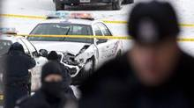 A damaged police car and police officers remain at the site where Police Sgt. Ryan Russell was struck by a stolen snowplow in Toronto on Jan. 12, 2011. An attempt to stop a stolen snowplow during a wild police chase through snowy city streets ended in tragedy Wednesday when an officer was struck by the vehicle and killed. (Chris Young/Chris Young/The Canadian Press)