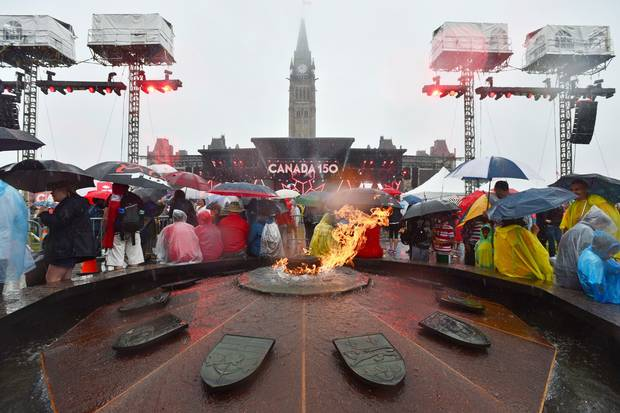 July 1, 2017: People take shelter from the rain on Parliament Hill in Ottawa during Canada 150 celebrations.