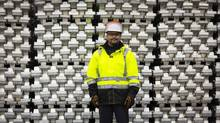 Gaby Poirier, general manager of B.C. operations, at the Rio Tinto Alcan Kitimat site with stacks of aluminum ingots. (John Lehmann/The Globe and Mail)