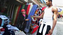 Houston Rockets player Tracy McGrady negotiates the price of cloth with a stall holder after a visit to the Great Wall of China at Mutianyu, north of Beijing Friday Oct. 15, 2004. (Associated Press)