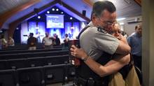RCMP Constable Jim Shields receives a hug from Elisabeth French after a church service at the Hillside Baptist Church on June 8. (FredLum/The Globe and Mail)