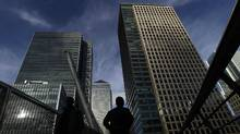 Silhouetted workers walk in front of office towers in the Canary Wharf financial district in London. (Luke Macgregor/Reuters/Luke Macgregor/Reuters)