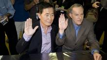 George Takei, left, and his partner Brad Altman raise their hands as they get their marriage certificate permit in West Hollywood, Calif. on June 17, 2008. (Hector Mata/The Associated Press)