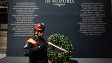 A rescue worker walks past a wall with the names of victims of the Jan. 31 explosion at the headquarters of state oil monopoly Pemex, in Mexico City Feb. 8, 2013. (TOMAS BRAVO/REUTERS)