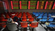 A lone Chinese investor monitors his stock prices at a securities firm in Hefei, in eastern China's Anhui province on October 10, 2011. (STR/AFP/GETTY IMAGES)