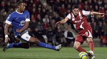 Cheltenham Town's Darren Carter, right, shoots under pressure from Everton's Sylvain Distin during the English FA Cup Third Round soccer match at the Abbey Business Stadium, Cheltenham England Monday Jan. 7, 2013. (Nick Potts/AP)