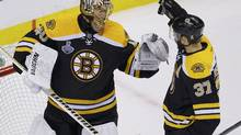 Boston Bruins' Patrice Bergeron (R) congratulates goalie Tuukka Rask after his shutout win over the Chicago Blackhawks in Game 3 of their NHL Stanley Cup Finals hockey series in Boston, Massachusetts, June 17, 2013. (Brian Snyder/Reuters)