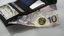 A Loonie and ten dollar bill are seen in this file photo. (Fred Lum/Fred Lum/The Globe and Mail)