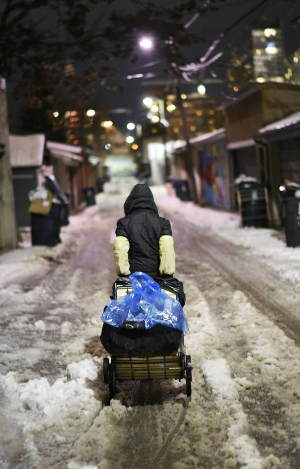 Wearing long sleeve protectors, a Chinese grandmother walks the streets of Toronto in search of wine and beer bottles with which to fill her buggy.