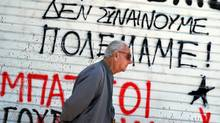 A man walks in front of a graffiti-covered wall in downton Athens on Sunday. The anti-austerity-plan slogan reads, 'We do not agree - We have war.' (Dimitar Dilkoff/AFP/Getty Images)