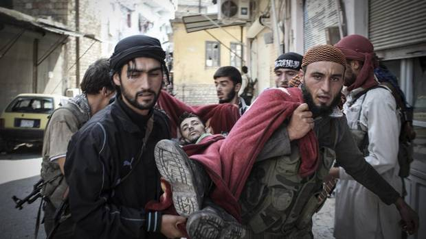 Syrian rebels carry a wounded comrade in a blanket away from the frontline in the town of Harem, Syria. Despite two weeks of attacking a Roman-era citadel in which pro-Assad militia are dug in, the rebels failed to secure the town. (Mustafa Karali/AP)