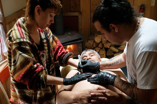 Cast member Russell Davis gets a traditional tattoo by artist Cory Bulpitt (right).