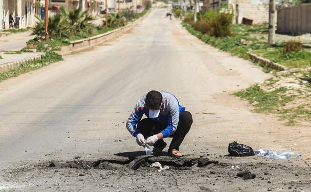 A Syrian man collects samples from the site of a suspected toxic gas attack in Khan Sheikhun, April 5, 2017.