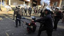 Riot police fire tear gas at protesters during clashes near Tahrir Square in Cairo, on Tuesday. (Khalil Hamra/AP)