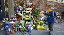 A toddler holds a boquet of orange flowers at a memorial to Jack Layton outside the late NDP leader's Toronto constituency office on Aug. 23, 2011. (Michelle Siu/Michelle Siu/The Globe and Mail)