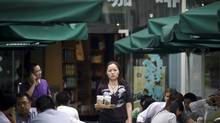 A woman takes out cups of coffee at a cafe in Beijing, China, Friday, June 24, 2011. (Andy Wong/AP)