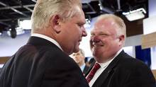 Mayor Rob Ford, right, laughs with his brother and campaign manager Doug Ford, left, during a commercial break as Rob Ford takes part in a live television mayoral debate in Toronto on Wednesday, March 26. (Nathan Denette/The Canadian Press)