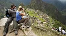 A tourist couple takes pictures of Inca's citadel of Machu Picchu in Cuzco. (Enrique Castro-Mendivil/Reuters)