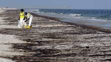 In this June 23, 2010 file photo, crews work to clean up oil from the Deepwater Horizon oil spill washed ashore at Pensacola Beach in Pensacola Fla. (Michael Spooneybarger/Michael Spooneybarger/Associated Press)