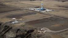 An oil drilling rig operates near homes and farm fields outside Williston, N.D. (JIM URQUHART/REUTERS)