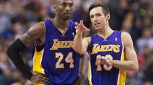 Los Angeles Lakers guards Kobe Bryant, right, and Steve Nash, right, talk during a time-out while playing against the Toronto Raptors during first half NBA basketball action in Toronto on Sunday, January 20, 2013. (Nathan Denette/THE CANADIAN PRESS)