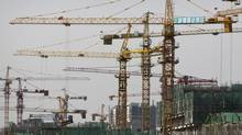 Cranes stand on a new residential construction site in Beijing on Thursday, Oct. 18, 2012. China's worst slump since the global financial crisis levelled out in the latest quarter. (Andy Wong/Associated Press)